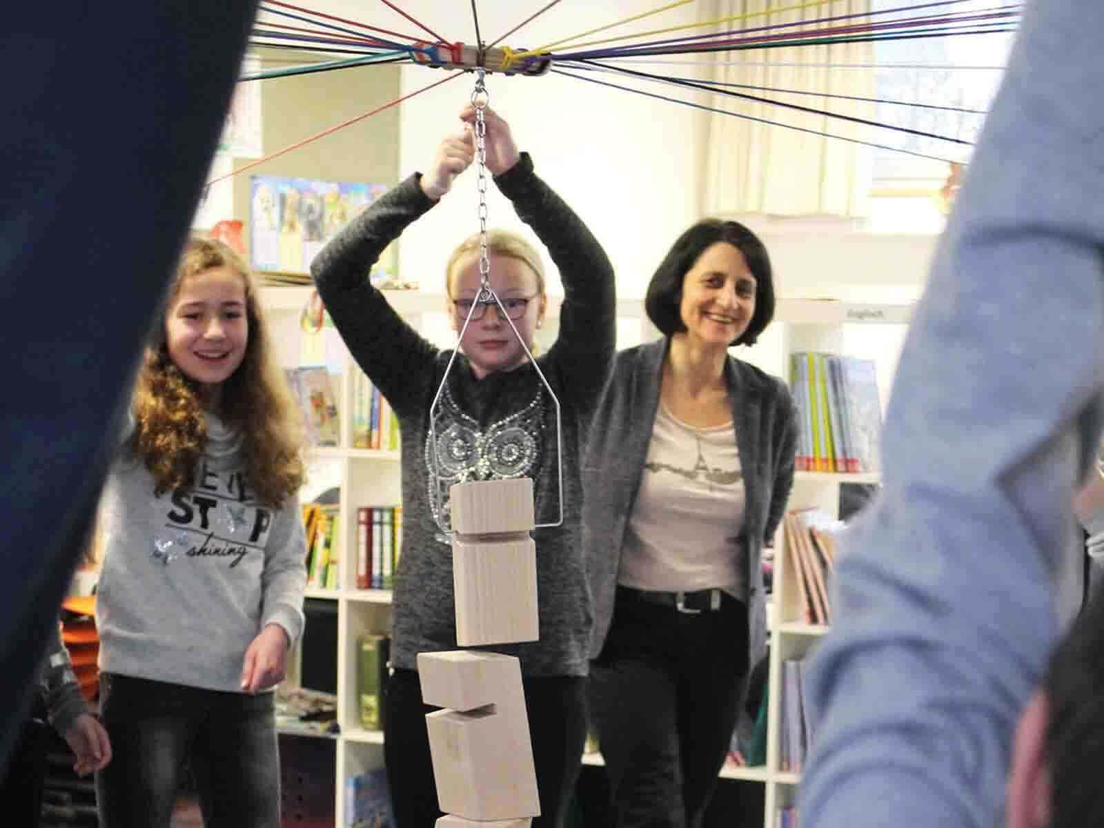 Andrea Janshen von den Sparkassenstiftungen Zukunft (re.) beobachtet die Schülerinnen und Schüler gespannt.