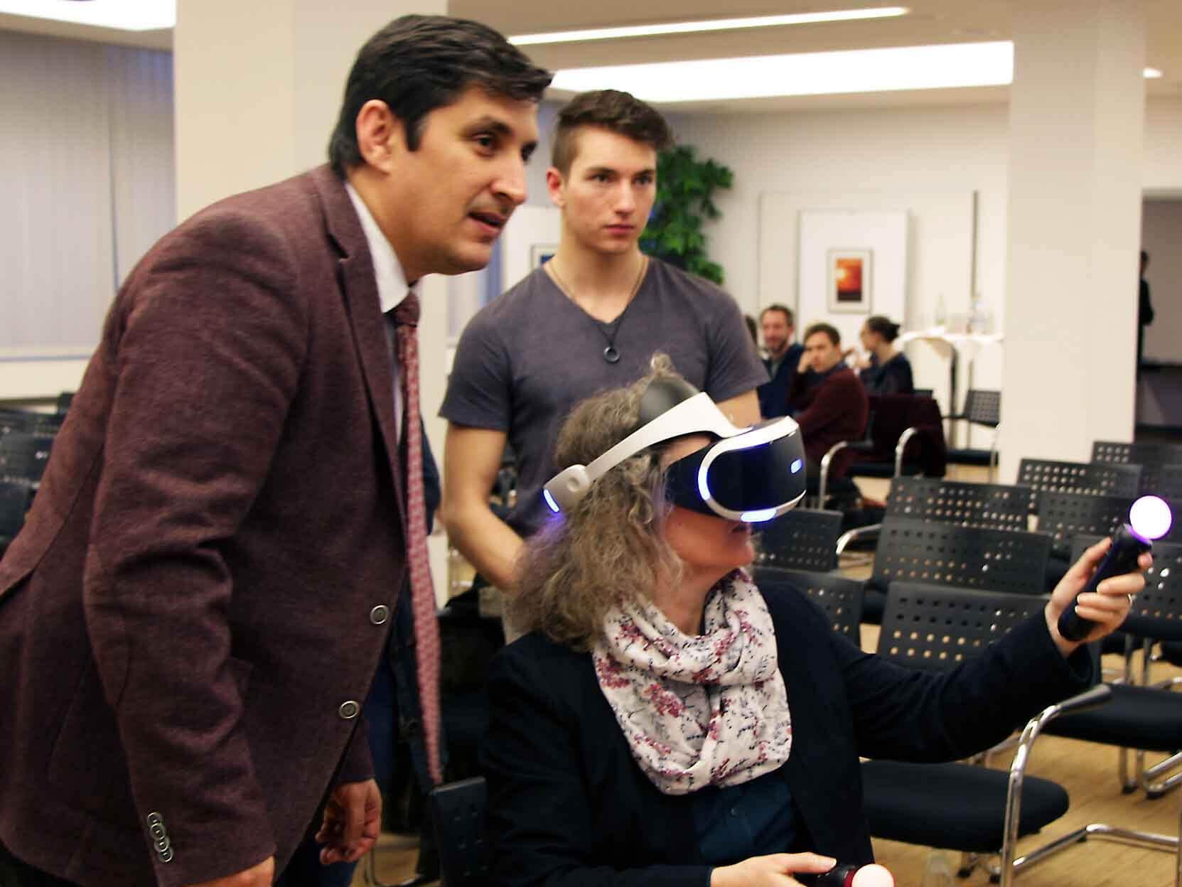 Cem Karakaya (li.) warnte vor den Risiken der VR-Brillen. Hier mit einer Teilnehmerin beim Testen einer VR-Brille.