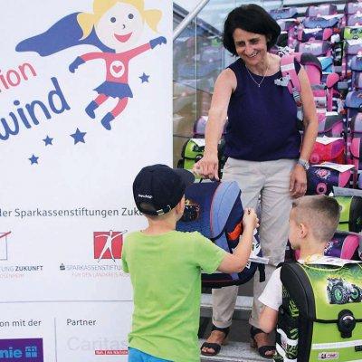 Andrea Janshen von den Sparkassenstiftungen Zukunftverteilt Schulranzen an ein paar neue ABC-Schützen.
