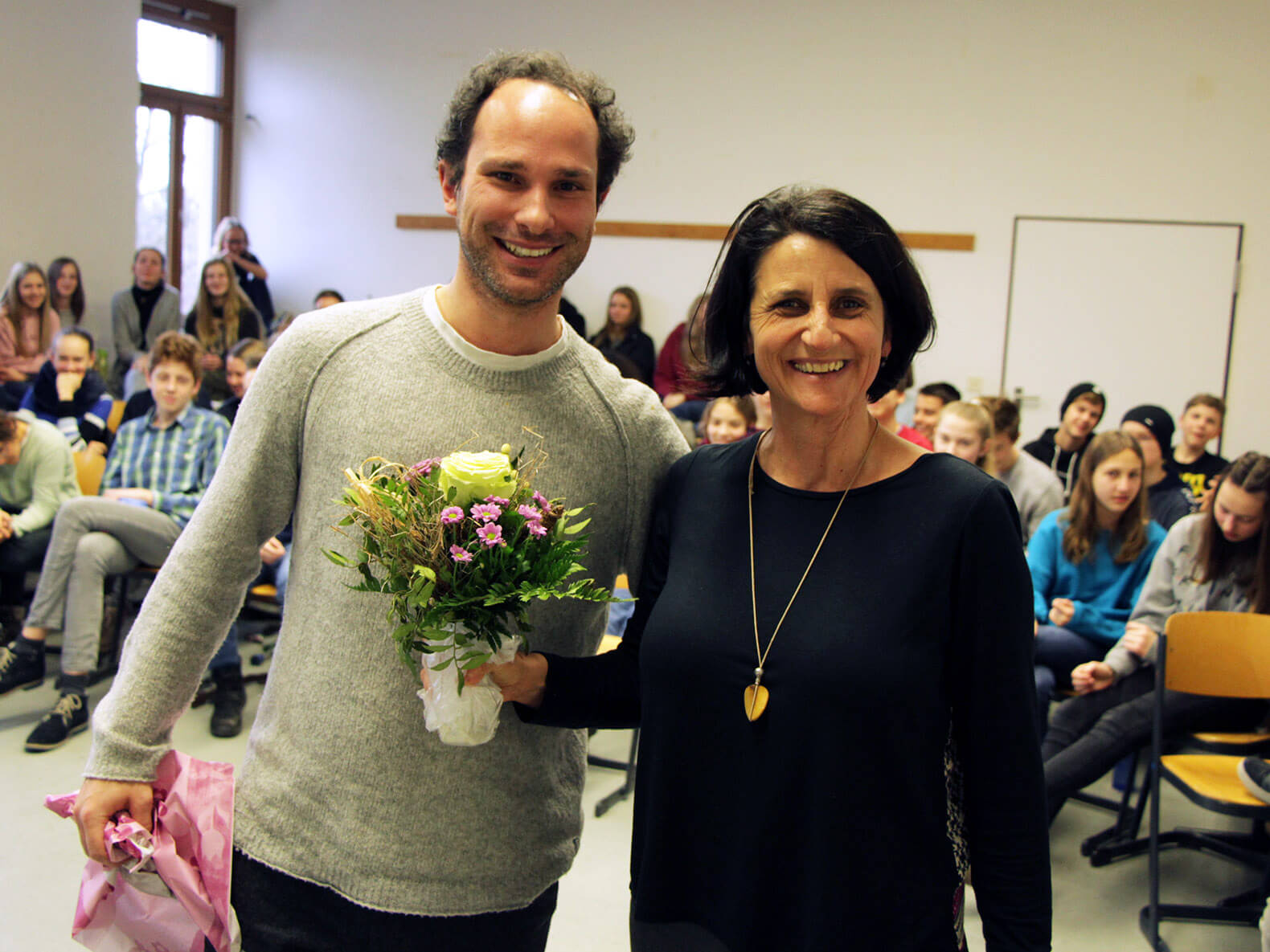 Benedikt Zimmermann (li.) überraschte Andrea Janshen von den Sparkassenstiftungen Zukunft (re.) bei ihrem Besuch mit einem Blumenstrauß.